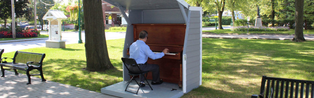 Photo d'un homme jouant sur le piano public en plein air
